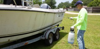 Man cleans boat with Wet & Forget concentrate in a pump sprayer