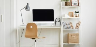 College dorm essentials including a desk, chair on rollers, desk lamp, clock and books