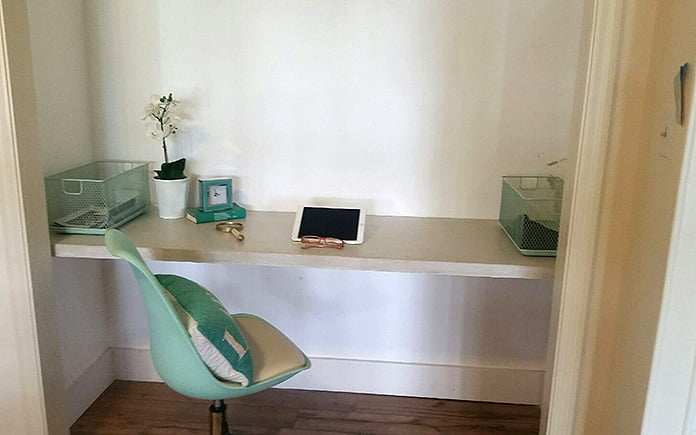 Concrete desk built into a small closet, hanging on French cleats