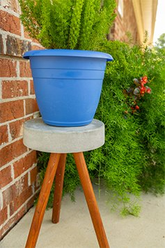 Concrete plant stand, as seen outside a beautiful brick home, surrounded by bushes