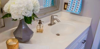 Cultured marble sink with a vase of flowers, a pump soap dispenser and an unlit candle