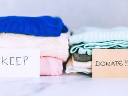Two piles of old clothes beside each other. In front of one pile is a sign that says, 'keep.' In front of the other pile is a sign that says, 'Donate.'