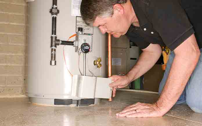 Man, on his knees, examining water heater before attempting a repair
