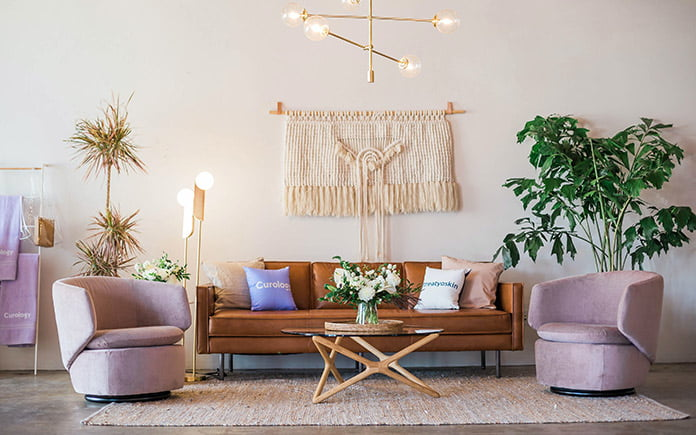 Mid-century living room with 1950s-era interior design including a macrame wall hanging, area rug, side chairs and retro sofa