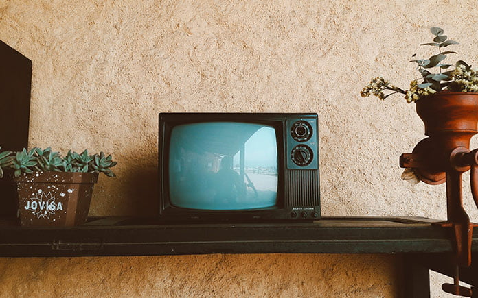 1960's television set on a shelf in a living room with dated wallpaper