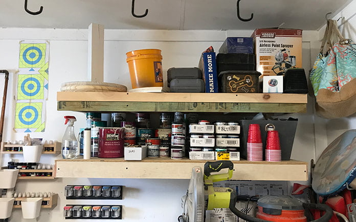 Paint cans stored on wood shelving in Sabrina and Bill Gordon's garage