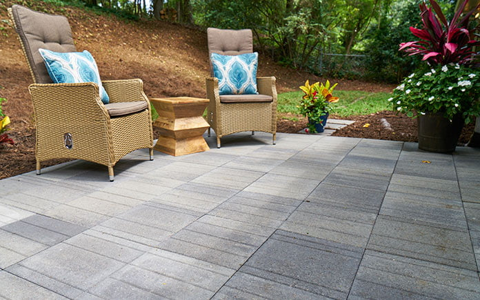 Wide view of Pavestone Avant Linear pavers on a patio with two lounge chairs.