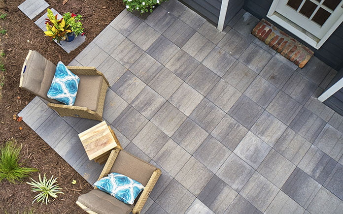 Pavestone Avant Linear pavers, as seen from an overhead view of a patio with two lounge chairs