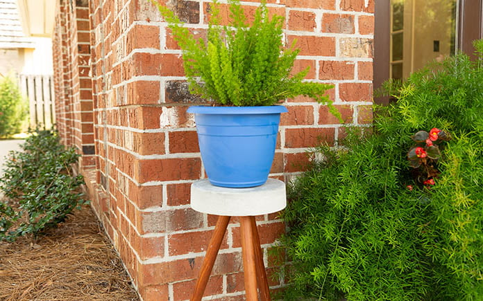 Plant stand made of three wood dowels and Quikrete concrete, outside, beside a brick home