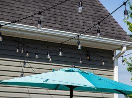 Cafe lights, seen over a patio umbrella near a home with vinyl siding