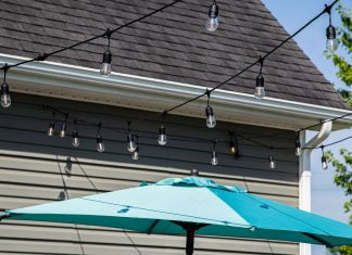 Cafe lights, seen over a patio umbrella near a home with vinyl siding