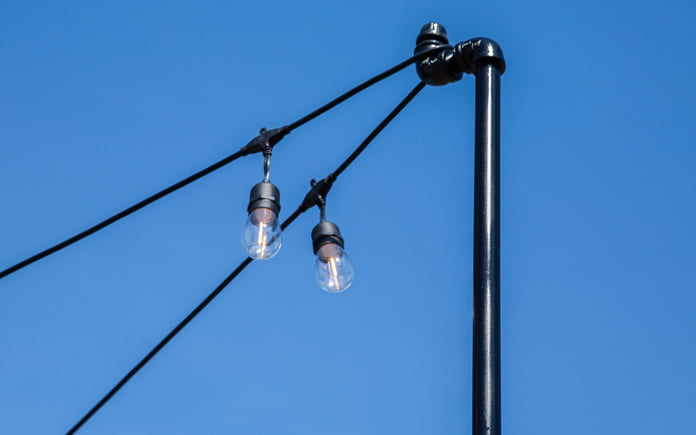 Closeup of a metal pole with a pipe fitting draped with cafe lights