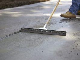 Man applies Quikrete Re-Cap Resurfacer to spalling concrete slab