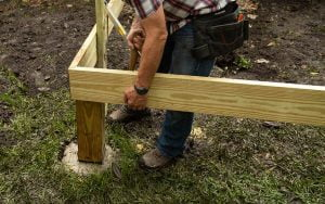 Danny Lipford installs wood deck post in concrete footing
