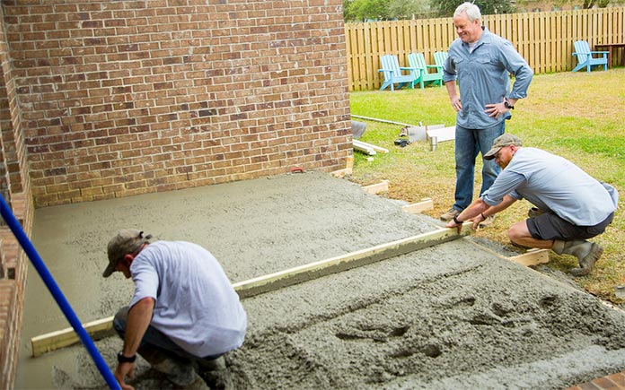 Danny Lipford oversees contractors as they pour a concrete slab for a patio.