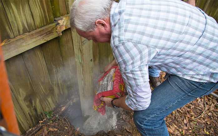 Demonstrating concrete DIY projects, Danny Lipford pours Quikrete Fast-Setting Concrete Mix into a hole of a sagging fence post