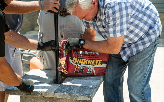 Danny Lipford pours Quikrete Fast-Setting Concrete Mix into the post hole