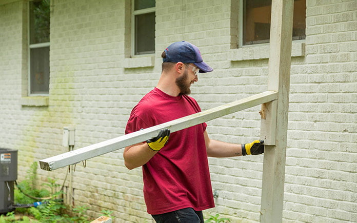 Denver Hawsey removes old porch railing from back of home