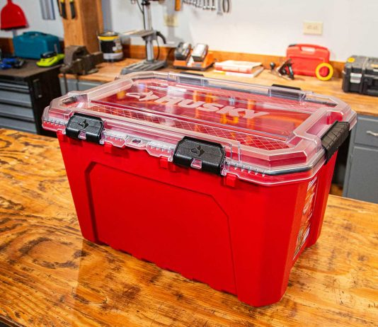 Husky's Professional-Duty Waterproof Storage Container, as pictured on a wood table in a workshop.