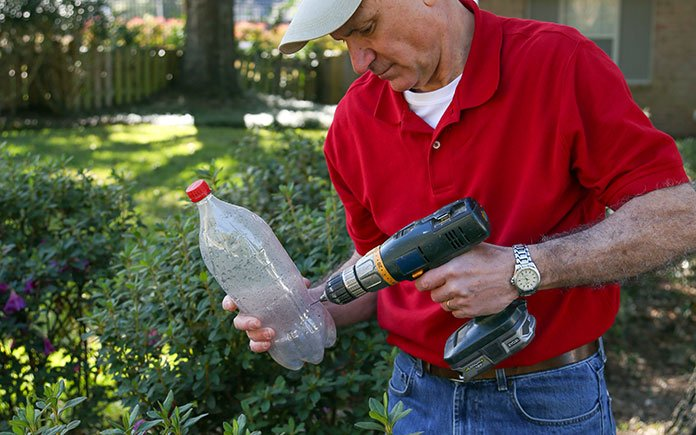 Joe Truini drills holes into a plastic soda bottle to make a DIY drip irrigation system