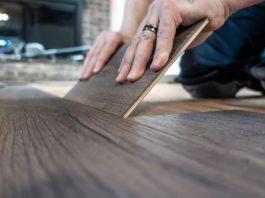 Closeup of man replacing a single plank of luxury vinyl flooring