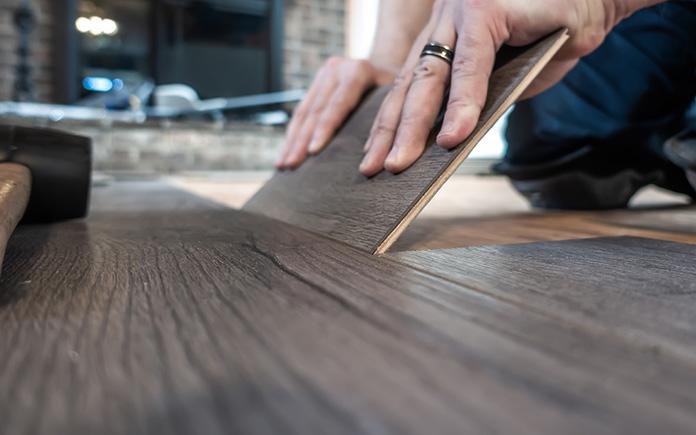 Closeup of man replacing a single plank of laminate flooring