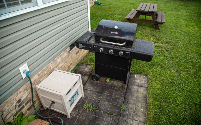 Old, outdated gas grill with folding table and wheels