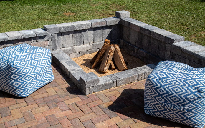Closeup of a paver patio with a paver fire pit in the corner