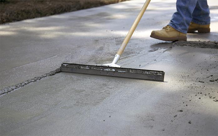 Man applies Quikrete Re-Cap Resurfacer to spalling concrete slab