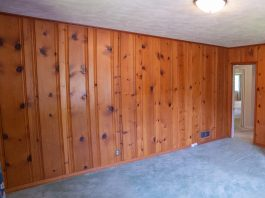 Dated wood paneling in a bedroom with unsightly carpeting