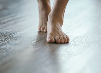 Bare feet, seen close up, walking on wood plank flooring installed over radiant heating system