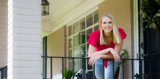 Chelsea Lipford Wolf, host of Today's Homeowner, stands beside wrought iron railing on her front porch.