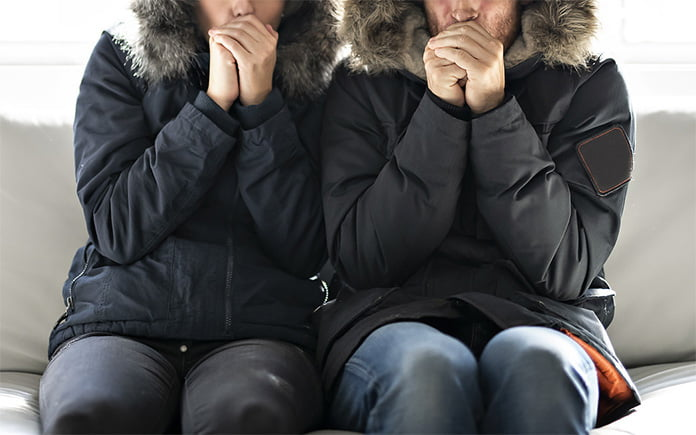 Couple, wearing parkas, shivering on their couch in their cold home during harsh fall weather