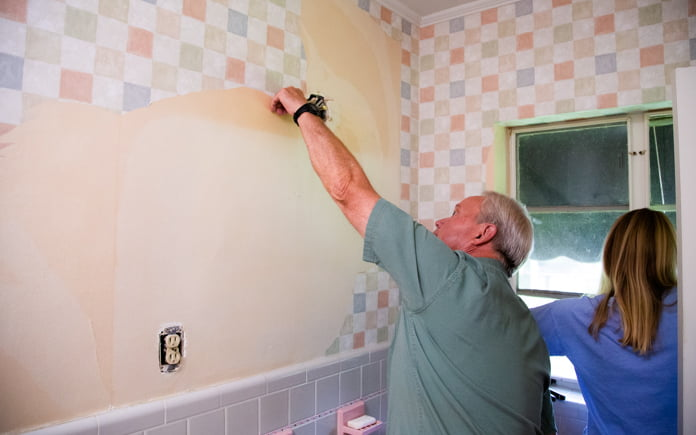 Danny Lipford and Chelsea Lipford Wolf remove wallpaper from a room in a ranch-style house