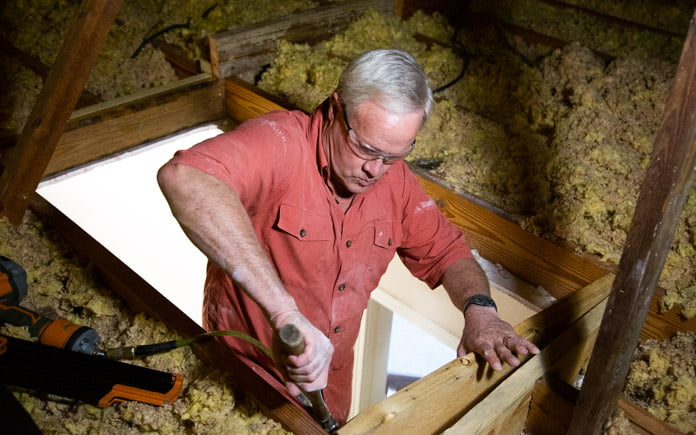 Danny Lipford, host of Today's Homeowner, installs attic stairs in a ranch-style house.