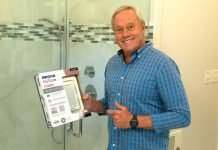 Danny Lipford, posed in this home bathroom, points to a box with a Broan-NuTone ventilation fan that he will install in his personal shower.