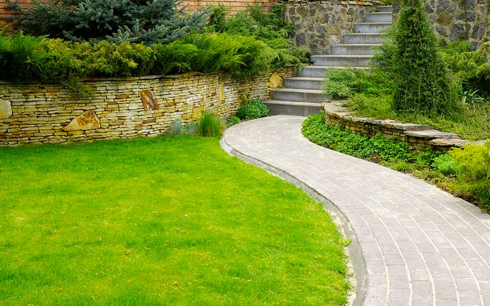 Lush backyard with stone path and retaining wall filled with plants and bushes