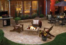 Hardscape features in a luxurious backyard, featuring a paver patio, Adirondack chairs, and an outdoor dining set