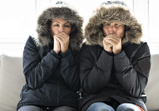 Couple, shivering cold, in home that has not heat during the chilly fall and winter