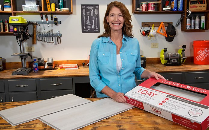 Jodi Marks, of Today's Homeowner, stands beside a box of Daltile QuicTile porcelain tiles in a workshop