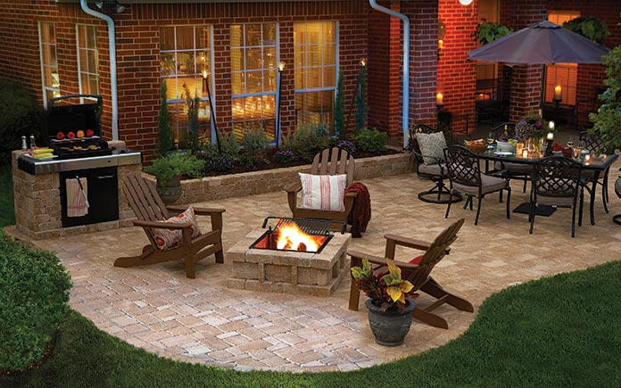 Brick home with a paver patio featuring a Pavestone RumbleStone fire pit, Adirondack chairs and an outdoor dining set with an umbrella