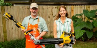 Jodi Marks and Dan, a Home Depot employee, hold DeWalt's blower and trimmer kit in a backyard.