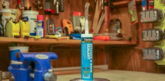 Tube of Titebond caulk sitting on a table in a workshop beside some plastic tubing