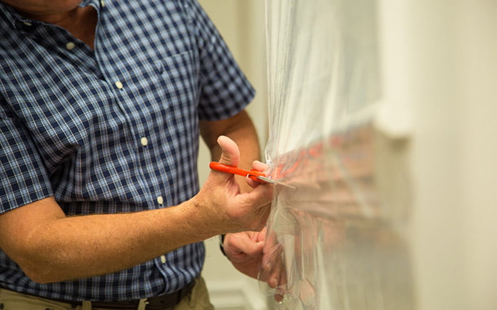 Today's Homeowner host Danny Lipford trims window film while he insulates a home before winter.