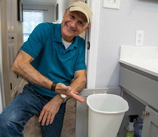 Joe Truini displays a trash can he installed inside a cabinet