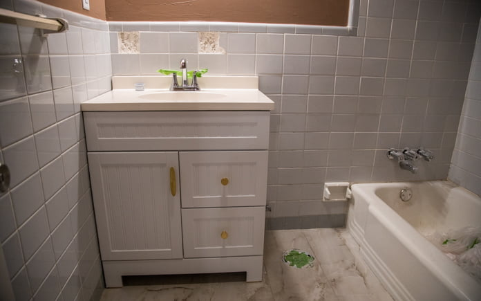 Partially remodeled bathroom with new vanity, gold drawer pulls and knobs and no toilet