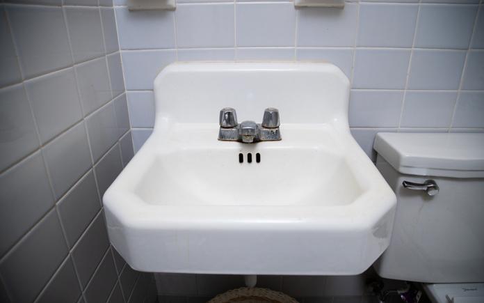 Old cast-iron sink in an unattractive mid-century bathroom