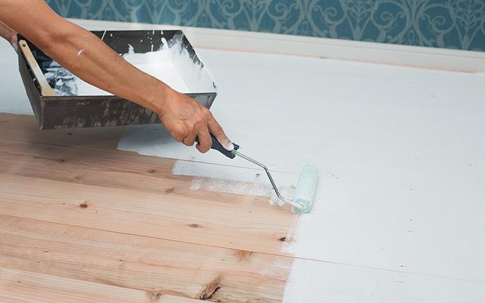 Woman paints hardwood floors white