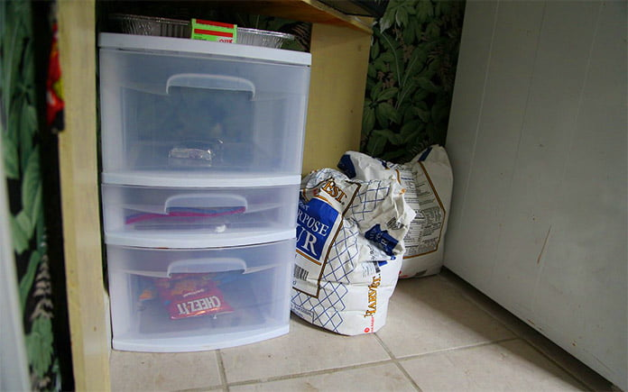 Plastic, two-tiered storage bins on the floor in a messy closet