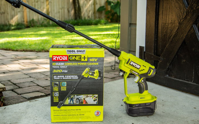 Ryobi's Cordless Power Cleaner is displayed on a table outside.